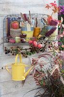 Wandhänger zum Aufbewaren von Utensilien: Bindegarn, Stecketiketten, Gießkanne, Kleingerät und Buch, Zieräpfel und Brombeerzweig als Deko