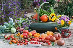 Erntetisch mit Tomaten, Kohlrabi, Gelbe Bete 'Burpees Golden', Zucchini, Hokkaido-Kürbis, Mangold, Sonnenblume und Strauß aus Aster und Ringelblumen