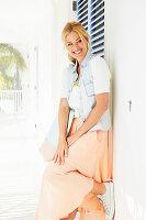 Blonde Frau in weißem T-Shirt, Jeansweste und Rock