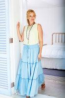 Blonde Frau in weißem Top und blauem Rock