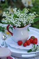 Maiglöckchenstrauß in Sahnekännchen auf Teller mit Erdbeeren