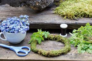 Zutaten für Vergißmeinnicht-Kranz: Vergißmeinnichtblüten, Storchschnabel-Blätter, Mooskranz, Schere und Wickeldraht