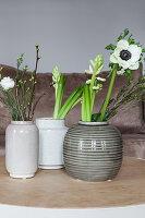Frühlingsblüten in Keramikvasen: Anemone, Waxflower, Hyazinthe, Milchstern, Prärieenzian und Kirschzweig