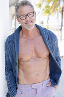 Grauhaariger Mann mit Bart und Brille in Strickjacke und Hose