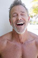 Gut gelaunter grauhaariger Mann mit Bart
