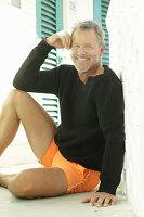 Grauhaariger Mann in schwarzem Pulli und orangefarbenen Shorts