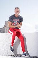 Grauhaariger Mann in T-Shirt und roter Sporthose
