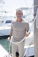 Grauhaariger Mann in hellem Outfit am Hafen