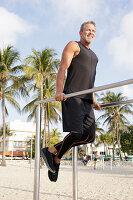 Grauhaariger Mann in schwarzer Sportbekleidung macht Sport auf dem Fitness-Parcours