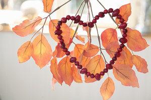 Hagebuttenherz auf künstlichem Zweig mit Herbstlaub
