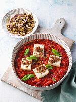 Ofenkäse auf fruchtiger Tomatensauce serviert mit Linsensalat