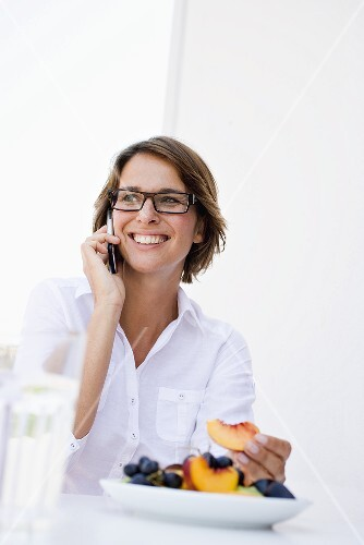Woman using mobile phone, plate of fruit