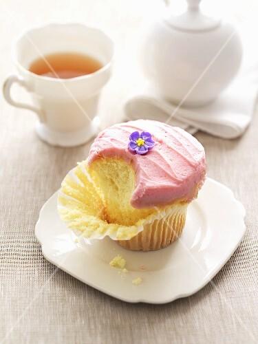 Partly-eaten cupcake with buttercream & sugar flower, tea