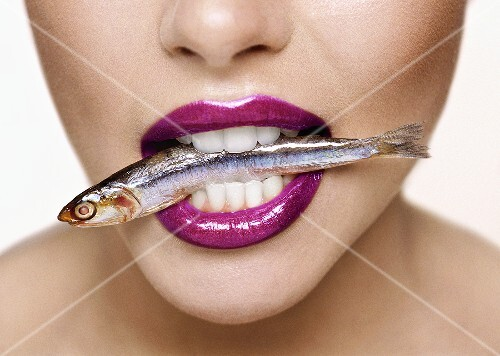 Woman with a sardine in her mouth