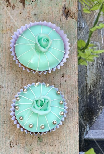 Two turquoise cupcakes with roses and silver dragees