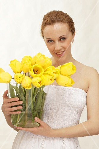 A woman holding a glass vase filled with yellow tulips