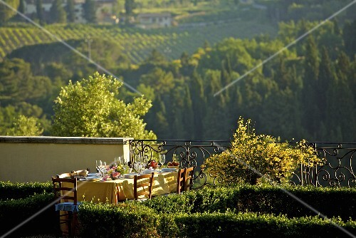 A table laid in a garden in Tuscany