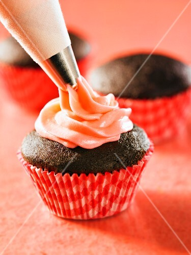A chocolate cupcake being decorated with cream