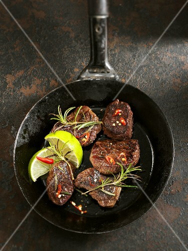 Kangaroo steaks with chilli peppers, limes and rosemary in a pan
