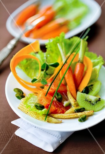 A mixed salad with carrots, baby corn cobs and kiwi