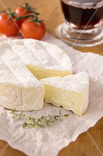 Camembert, sliced, on paper with tomatoes and a glass of red wine