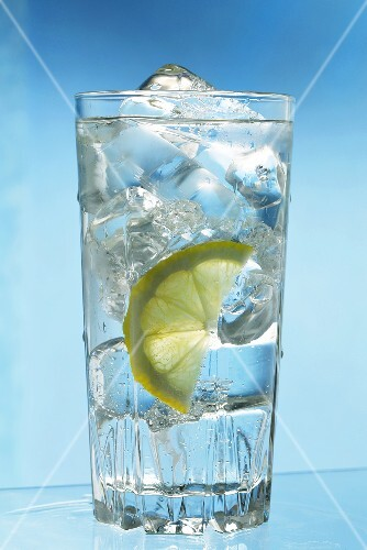 A glass of water with ice cubes and a slice of lemon