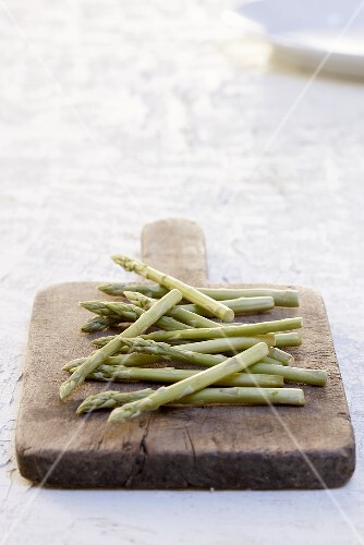 Green asparagus on an old cutting board
