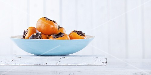 Several persimmons in a bowl