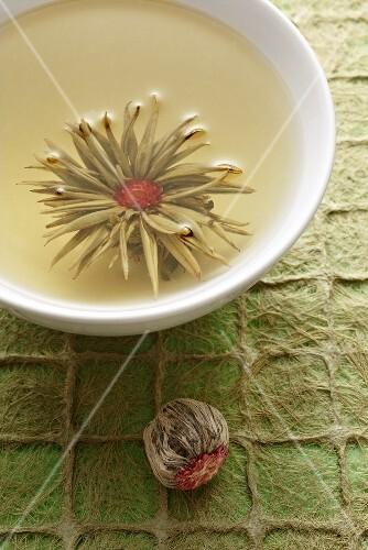 A bowl of jasmine tea with a tea rose