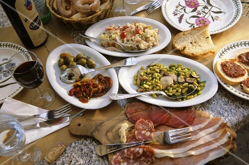 Laid table with antipasti and red wine, Tuscany