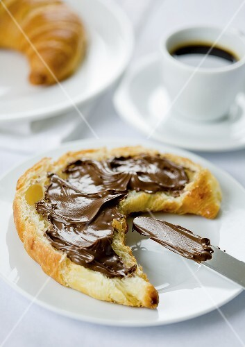 Croissant spread with chocolate and an espresso