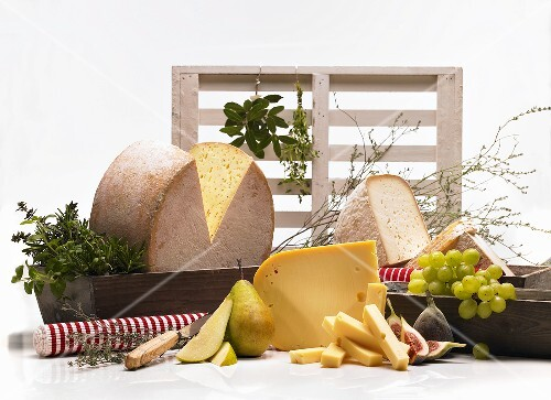 An arrangement of cheeses with fruit and herbs