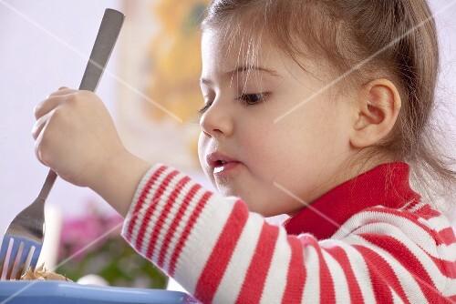A little girl eating chicken
