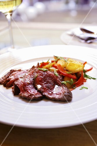 Minute beef steaks with potatoes, pepper and spring onions