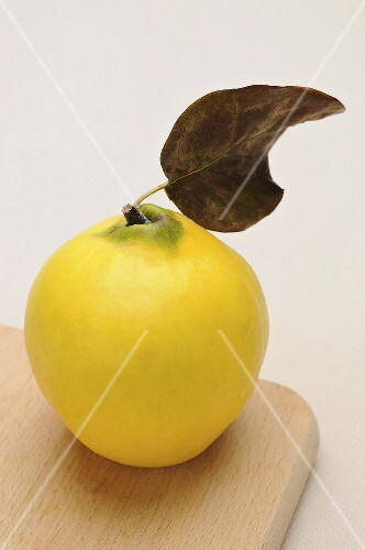 A quince with a leaf on a chopping board