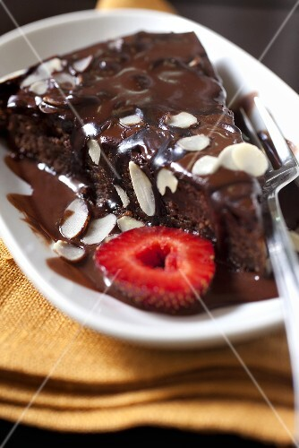 A piece of chocolate cake with chocolate sauce, slivered almonds and strawberries