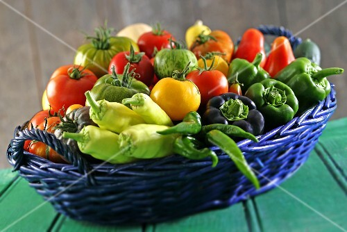 A basket filled with tomatoes and peppers