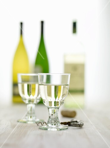 Glasses of white wine, a cork screw and bottles of wine