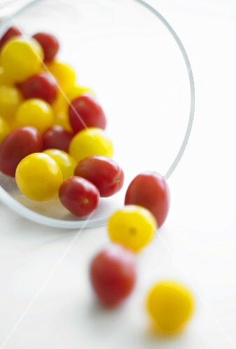 Red and yellow cherry tomatoes falling out of a glass