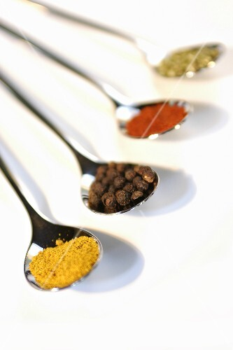 Spoons of curry, allspice, paprika and dried parsley