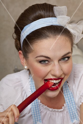 A retro-style girl bitting into a stalk of rhubarb