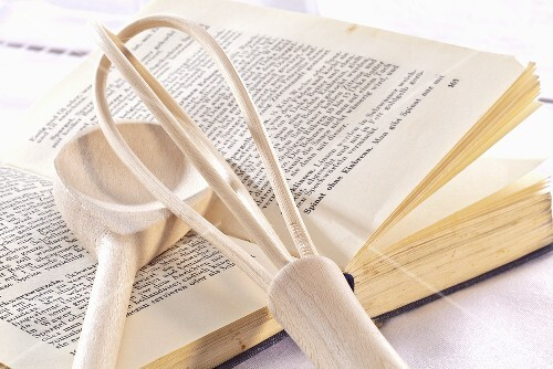 A cookbook, a whisk and a wooden spoon