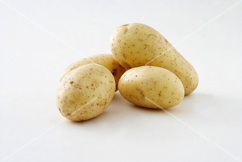 Four Potatoes Stacked on a Weathered Table