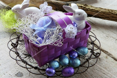 A basket of Easter eggs, porcelain rabbits and chocolate eggs