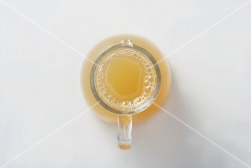 Naturally cloudly apple juice in a glass jug, seen from above