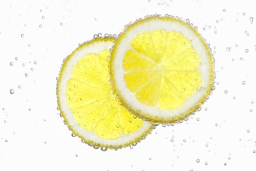 Two lemon slices in water with air bubbles