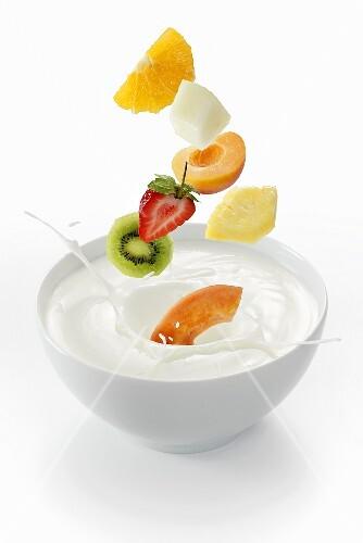Fresh fruit falling into a bowl of yogurt