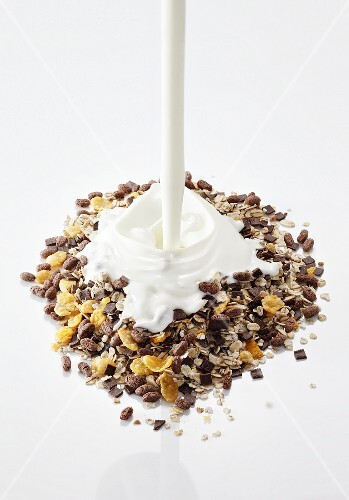 Yogurt being poured onto muesli