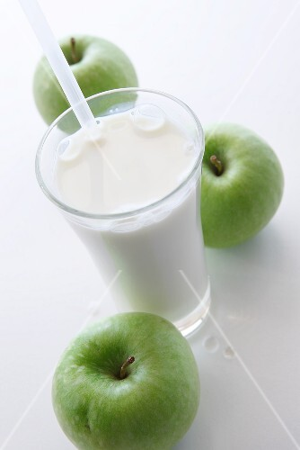 A glass of milk with a straw and three green apples