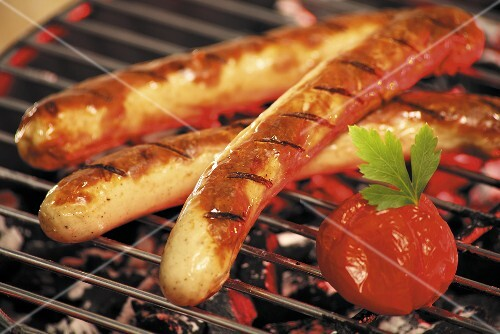 Grilled sausages and tomatoes on a barbeque